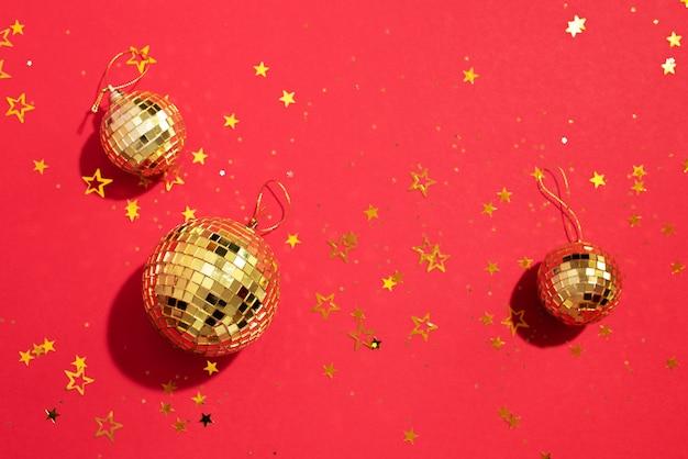 赤の背景に光沢のある星と黄金のクリスマスボール
