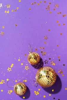 紫色の背景に光沢のある星と黄金のクリスマスボール