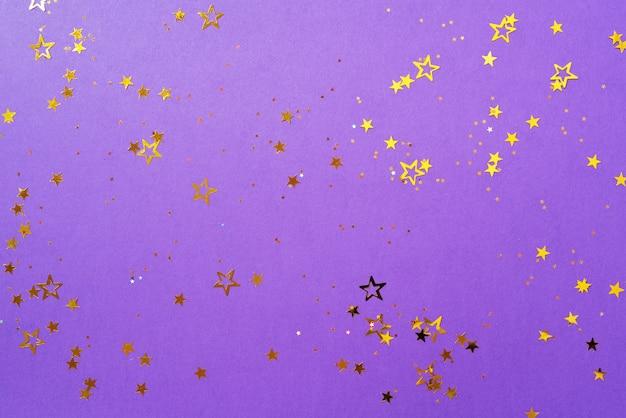 Золотая звезда сверкает на фиолетовом фоне
