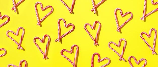 黄色の背景にハート形のキャンディー杖のクリスマスのパターン