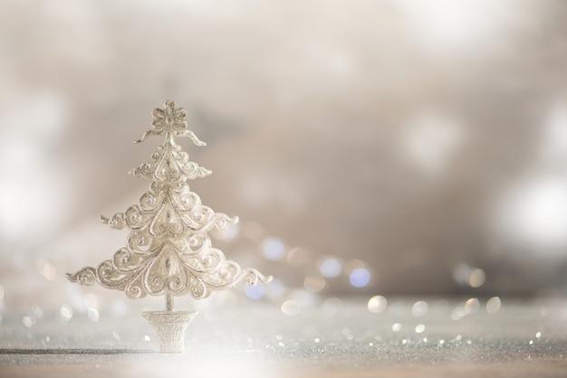 ライトのボケ味、コピー領域と灰色の背景に銀のキラキラクリスマスツリー。