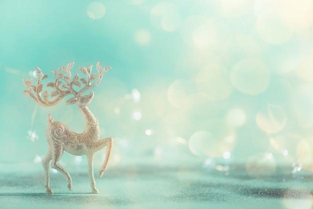 ライトのボケ味、コピー領域と青い背景に銀のキラキラクリスマス鹿。