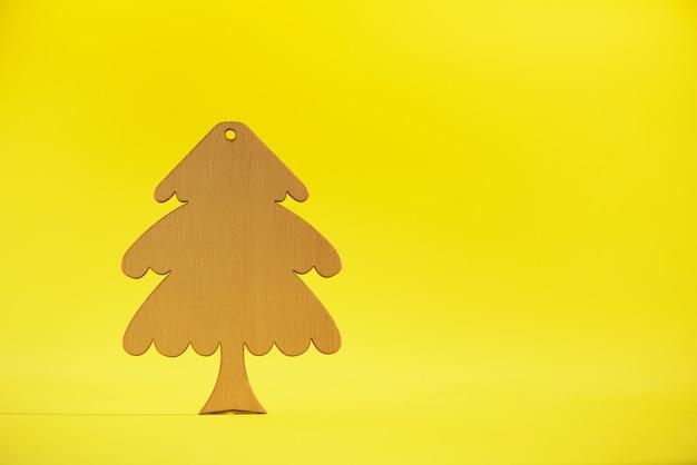 Деревянная рождественская елка на желтом фоне с копией пространства. новогодняя вечеринка. концепция зимнего отдыха.