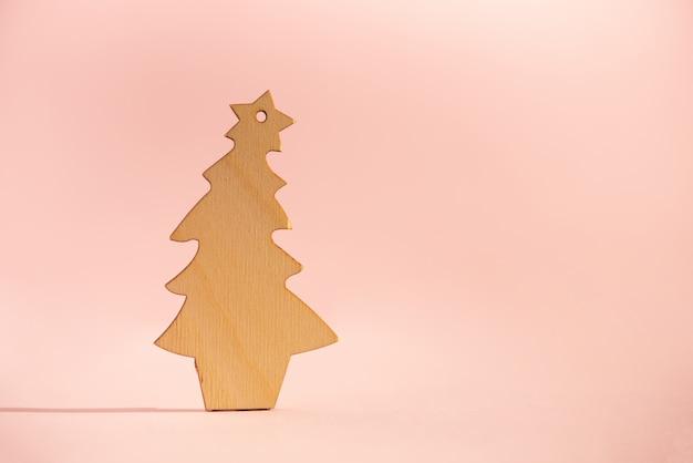 Деревянная рождественская елка на розовом фоне с копией пространства. новогодняя вечеринка.