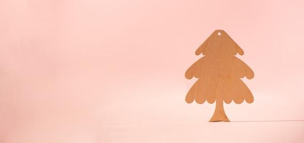 Деревянная рождественская елка на розовом фоне с копией пространства.