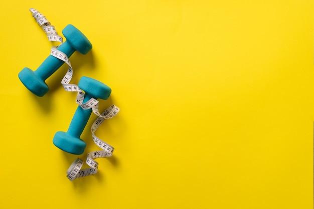 フィットネス、ダンベルと黄色の背景上の測定テープを持つスポーツコンセプト。