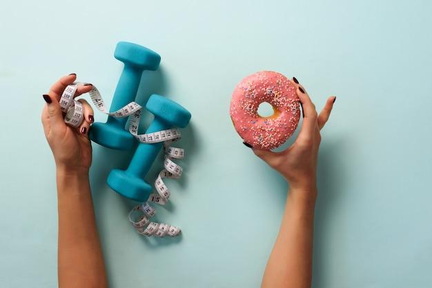測定テープ、青い背景にダンベル、甘いドーナツを持つ女性の手。