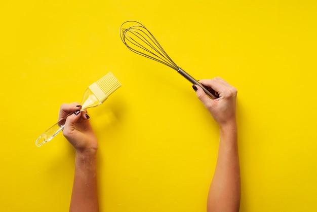 黄色の背景に台所用品を持つ女性の手。ベーキングツール - ブラシ、泡立て器、ヘラ。パン屋さん、料理、健康的な自家製食品のコンセプトです。コピースペース