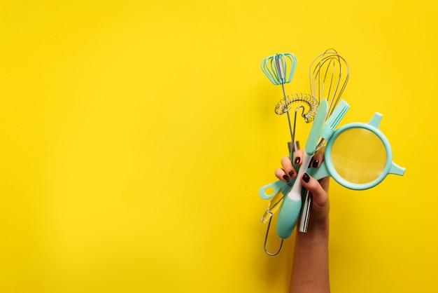 平置き焼きます。黄色の背景に女性両手キッチンツール、ふるい、麺棒、ヘラ、ブルッシュ。コピースペースバナー