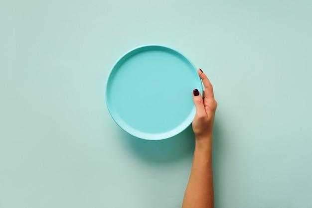 コピースペースとパステル調の背景に空の青いプレートを持っている女性の手。健康的な食事、ダイエットの概念バナー