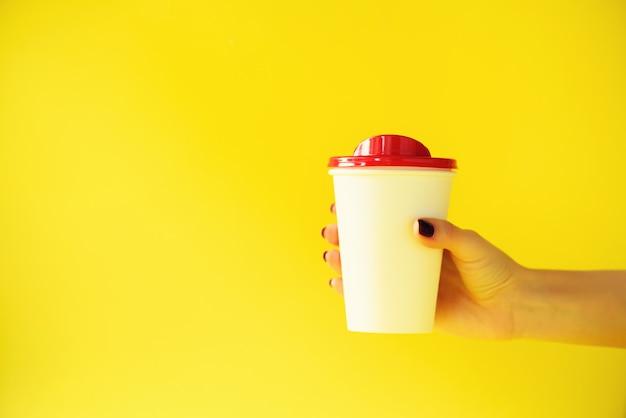 黄色の背景にホワイトペーパーマグカップを持っている女性の手。