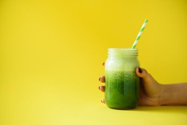 緑のスムージー、黄色の背景に対してフレッシュジュースのガラス瓶を持つ女性の手。