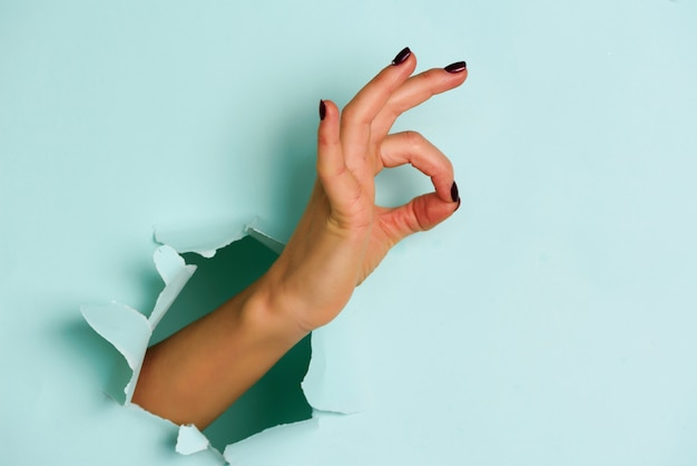 Женская рука показывая совершенный жест, да против голубой предпосылки.