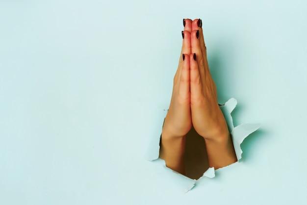 破れた青い紙の背景を通して若い女性の手を祈ってください。