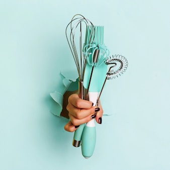 青い背景に台所用品を持つ女性の手。