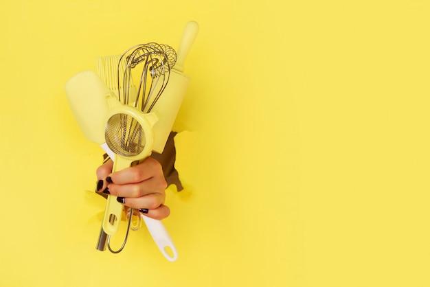 黄色の背景に台所用品を持つ女性の手。