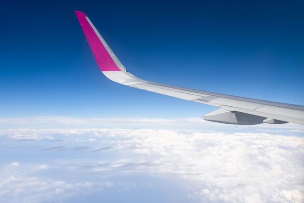 旅行の概念空の雲の上を飛んでいる飛行機の翼。コピースペース