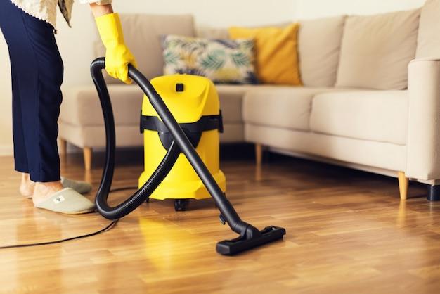 黄色い掃除機でソファを掃除する女性。スペースをコピーします。清掃サービスのコンセプト