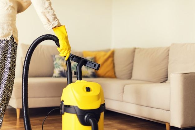 Софа чистки женщины с желтым пылесосом. копировать пространство концепция уборки