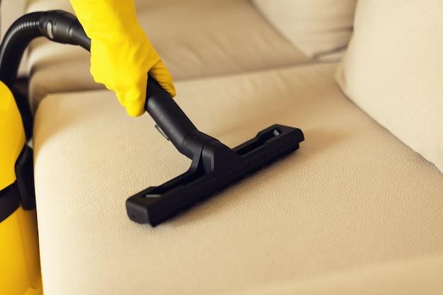 Софа чистки женщины с желтым пылесосом. копировать пространство чистая концепция