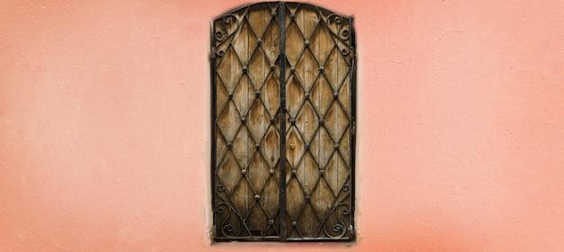 コピースペースとピンクの壁に古い木製と金属製のドア。テクスチャ背景ポップアートのコンセプト、ビンテージスタイル