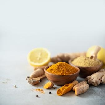 ウコンラテのための原料。ターメリックパウダー、ウコンの根、シナモン、生姜の灰色の背景。