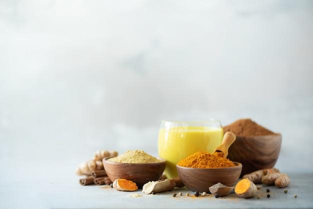 健康的なビーガンターメリックラテまたはゴールデンミルク、ターメリックルート、生姜粉、灰色のコンクリート背景に黒胡椒。