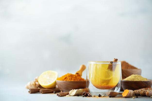 灰色の背景にウコンホットティーのための原料。レモン、生姜、シナモン、ウコンと健康的なアーユルヴェーダドリンク。