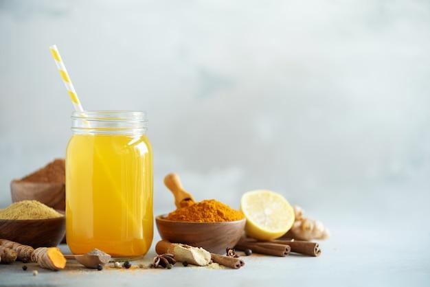 しょうが、ウコン、黒胡椒のレモン水。ビーガンホットドリンクのコンセプトです。灰色のコンクリート背景にオレンジ色のウコンドリンクのための原料