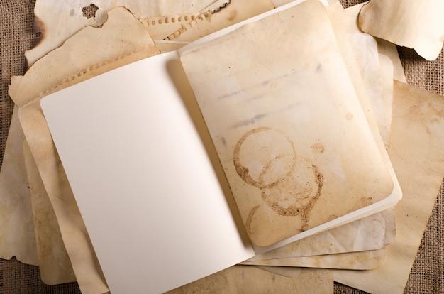黄麻布、荒布の上の古い紙とノートをスタックします。ビンテージとレトロのデザイン効果
