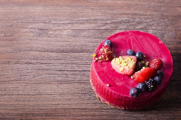 新鮮なイチゴ、ラズベリー、ブルーベリー、スグリ、ピスタチオの木製テーブルの上のおいしいラズベリーケーキ。