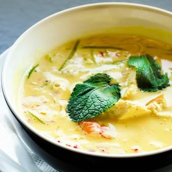 Острый кокосовый крем-суп с карри с курицей, тигровыми креветками, длинной соевой лапшой, ростками фасоли, лаймом, перцем чили и мятой.