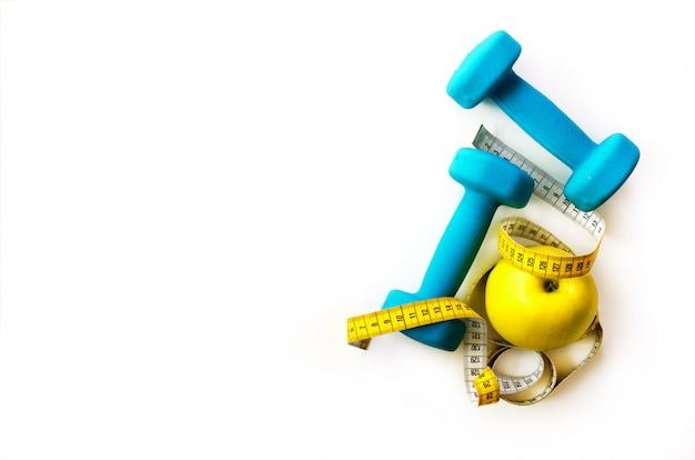 フィットネスの概念ターコイズ色のダンベル、黄色い測定テープ、新鮮なリンゴ。食事、スポーツ、健康的なライフスタイル。女の子のための春のトレーニング。