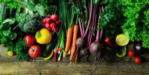 木製の背景に野菜。有機食品、ベジタリアンのコンセプト