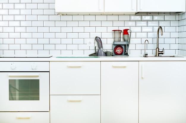 白のミニマルなキッチンインテリアとデザイン。タイル張りの壁