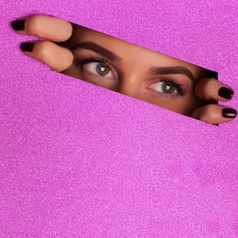 紫色の紙の背景に穴を通して見る明るいメイクアップを持つ少女