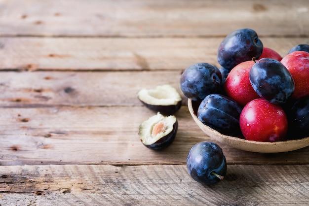 Голубые и розовые органические сливы на темное деревянном.