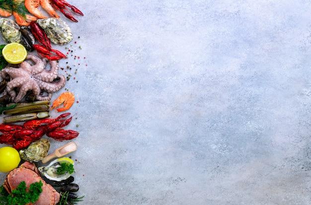 シーフードの背景 - 新鮮なムール貝、軟体動物、カキ、タコ、かみそりの殻、エビ、カニ、ザリガニ、ザリガニ、海藻、レモン、スパイス。
