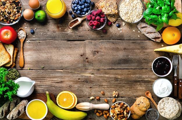 健康的な朝食食材、フードフレーム。グラノーラ、卵、ナッツ、フルーツ、ベリー、トースト、牛乳、ヨーグルト