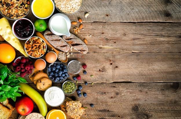 健康的な朝食食材、フードフレーム。グラノーラ、卵、ナッツ、フルーツ、ベリー、トースト、牛乳、ヨーグルト、オレンジジュース