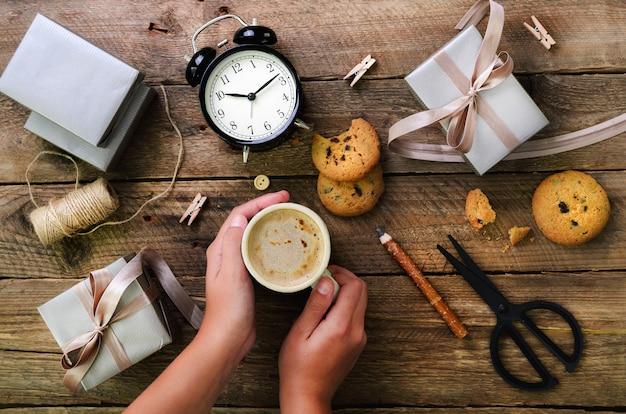 美しい女性両手木製のギフトボックス。黒の目覚まし時計、ペン、はさみ。