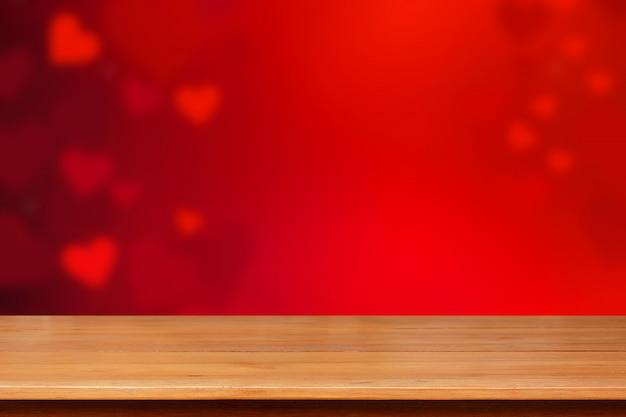 赤いハートの抽象的な背景 - バレンタインデーのコンセプトの上の木のテーブルトップ