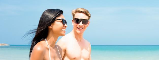 夏のビーチを歩いている若い異人種間の観光客カップル