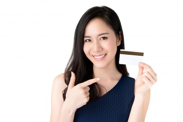 クレジットカードを手で提示する若い笑顔の美しいアジアの女性