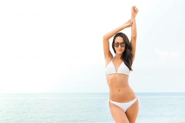 Бикики молодой красивой азиатской женщины нося представляя на пляже в лете