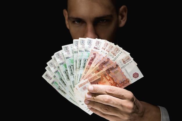 暗闇の中でお金、ロシアルーブル通貨を示す謎の男
