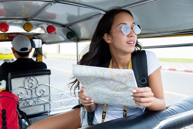 Женщина турист путешествует на местном такси тук тук в бангкоке, таиланд