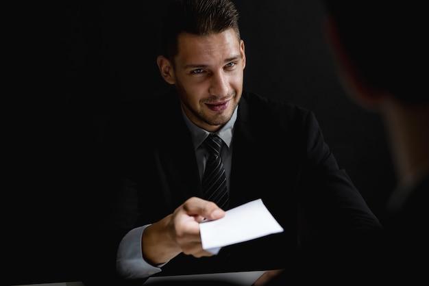 パートナーに封筒に賄賂のお金を提供している実業家