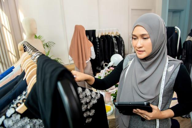 テーラーショップで働くスタートアップ事業主としてのイスラム教徒の女性デザイナー