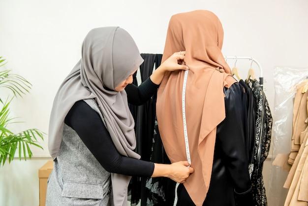 顧客の背中を測定する女性のイスラム教徒のデザイナー